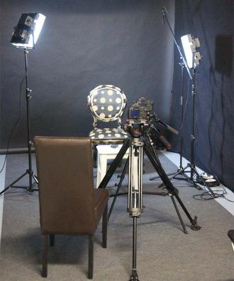Der leere Stuhl bei den Dreharbeiten zwischen zwei Scheinwerfern und hinter einer Kamera