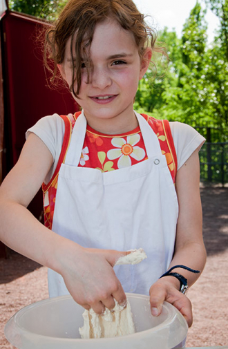 A girl in a kitchen apron kneading dough.