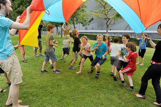 Kinder und Betreuer*innen spielen im Garten mit einem Schwungtuch
