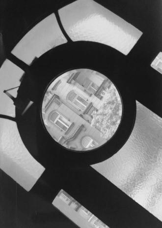 schwarz-weiß-Foto: Blick durch ein Sprossenfenster auf die gegenüberliegenden Häuser