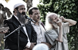 Film still of three men performing into a microphone, the men sing and play instruments