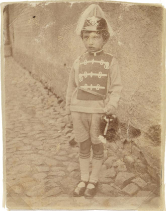 Photography of Walter Frankenstein as a child, costumed on cobblestones standing in front of a house wall