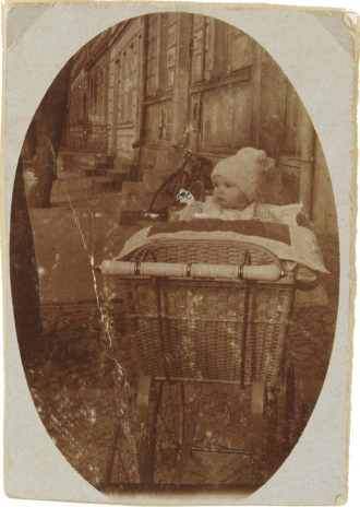 The portrait-format, oval vignetted photograph shows an infant (Walter Frankenstein) in a pram made of braided basket.
