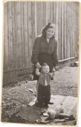 Die Aufnahme zeigt ein Kleinkind, welches von einer Frau an den Händen gehalten wird (Schwarz-Weiß-Fotografie)
