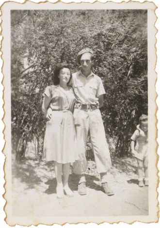 On the black and white picture Walter Frankenstein holds his wife Leonie in his arms. He wears a military uniform, Leonie a summer dress. They do not smile. Bushes grow in the background.