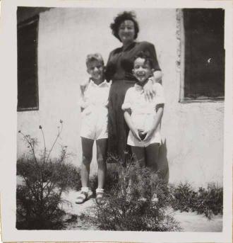 Auf der Schwarz-Weiß-Fotografie legt Leonie im dunklen Kleid ihre Hände auf die Schultern der links und rechts stehenden und in weißen Shorts und Hemden gekleideten Kinder. Im Hintergrund ist eine Hauswand zu sehen.