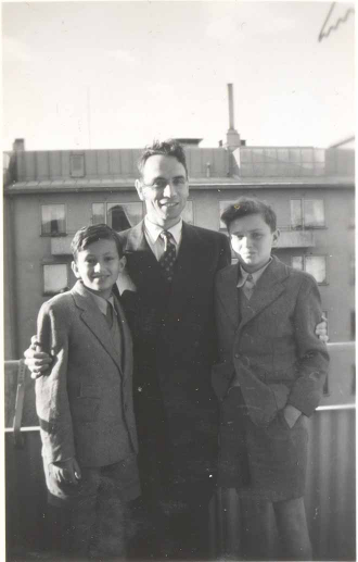 Rolf Rothschild stands in the middle of the black-and-white photo with his arms around the two boys. All three are wearing suits.