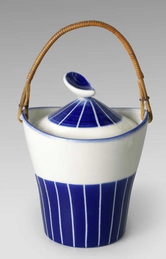Ceramic blue and white vessel with a stripe pattern and a straw handle