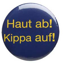 "Blue circular button with the yellow german text ""Haut ab! Kippa auf!"" written on it"