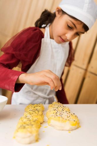 A girl sprinkles sesame onto the bread