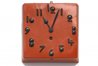 A red square clock with black numbers, the hand points to a few minutes past 11 o'clock