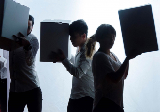 Junge Leute halten Kartons während einer Performance hoch