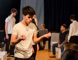 Junge Leute stehen im Raum und proben für eine Aufführung