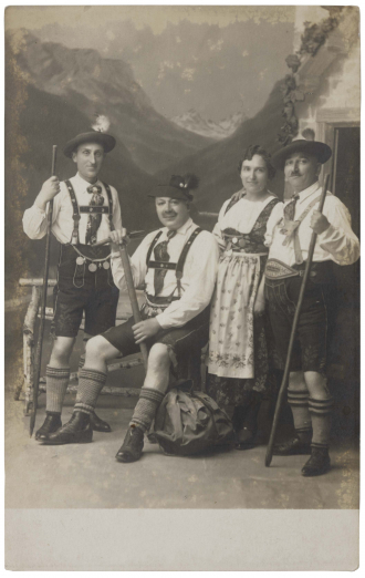 Black-and-white photograph of four people in traditional Bavarian costumes