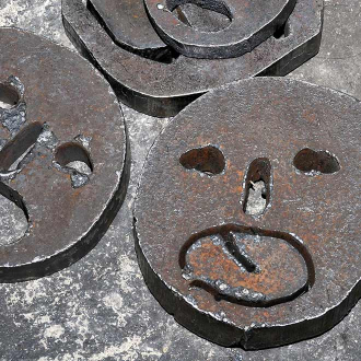 Close-up of faces cut into metal discs.