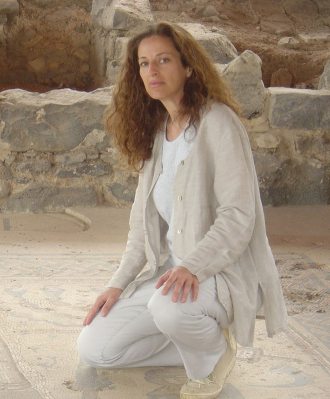 A woman on a mosaic floor in front of ruins