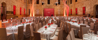 Glass Courtyard lit up with red and white lights, large dinning tables decorated with red flowers, silverware, and wine glasses fill the courtyard