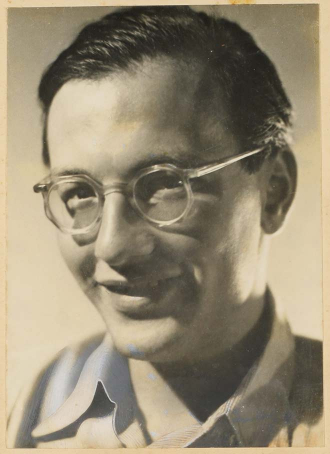 Black-and-white photograph of a young man with eyeglasses, smiling into the camera (half profile)