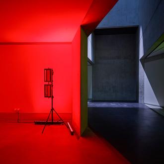 Ein Raum mit verwinkelten, kahlen Betonwände, der durch den Kontrast von rotem Licht und Schatten eine dramatische Wirkung entfaltet.