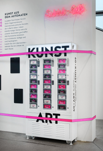 """A large white vending machine with the word """"ART"""" in black bold letters on it, the small compartments of the vending machine say """"Buy Me"""""""