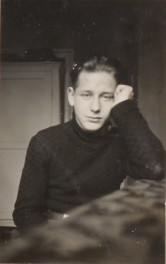 Black-and-white portrait photograph of a young man looking straight into the camera. His temple is propped up by the first of his left hand, his elbow resting on the table, where he is seated.