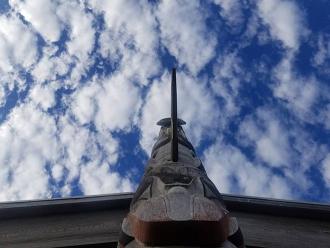 Fotografie eines Totempfahls vor wolkigem Himmel