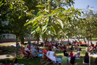 Besucher in Liegestühlen und auf Decken sitzend im Museumsgarten des Jüdischen Museums Berlin