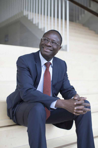 Karamba Diaby is sitting on a staircase, wearing a blue suit with a red check tie.