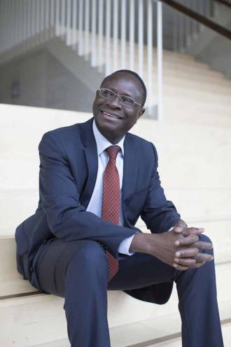 Karamba Diaby sitzt auf einer Treppe, er trägt einen blauen Anzug mit rotkarierter Krawatte.