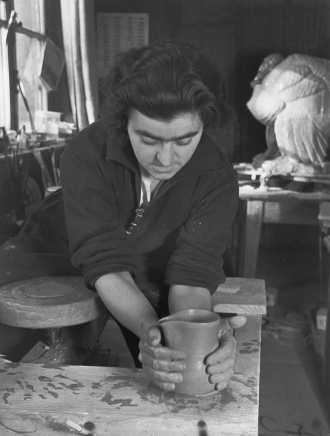 Black and white photo of a woman at the pottery wheel shaping a cup with her clay covered hands