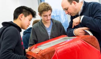 Zwei Schüler betrachten zusammen mit dem Guide einen Austellungs-Würfel