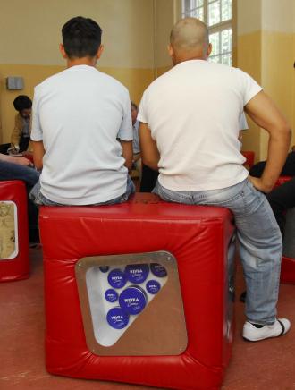 Zwei Männer sitzen auf einem roten Würfel
