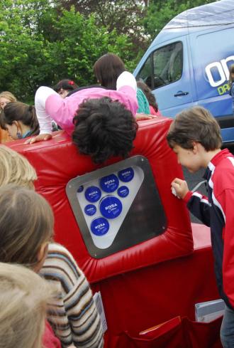 Kinder sind um und auf den mobilen Ausstellungswürfeln versammelt. Darin entdecken sie unterschiedlich große Nivea-Dosen.