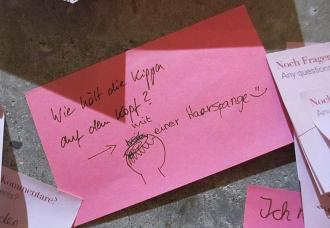 """Ein pinker Post-it-Zettel beschriftet mit """"Wie hält die Kippa auf dem Kopf? mit einer Haarspange :-)"""""""