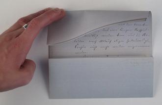 Eine Hand faltet einen Brief zusammen