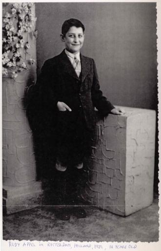 Porträt von Rudolf Appel stehend in einem Fotostudio. Er trägt eine dunklen Anzug, kurze Hosen mit Kniestrümpfen.