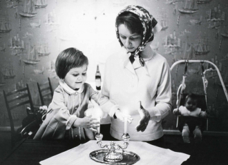 A young girl and a woman standing in front of candles.