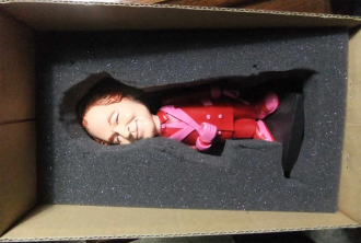 Red-haired doll in a box with styrofoam