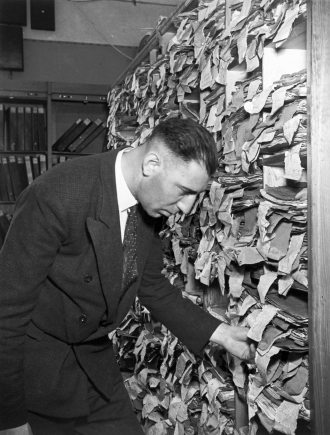 Black-and-white photo of a man in front of a shelving unit overflowing with file folders