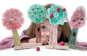 Girl behind paper trees