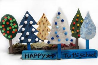 Fünf bunte, gebastelte Bäume auf einem Sockel mit der Aufschrift »Happy Tu bi-schwat«