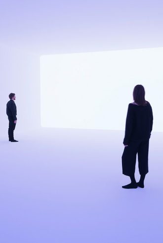 Ein Mann und eine Frau stehen in einem hellblau erleuchteten Raum und blicken auf eine weiße Wand
