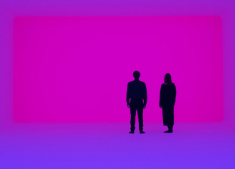Two people are standing in a room of blue and violet light.