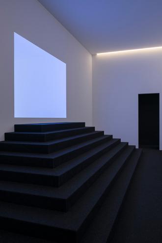 Eine dunkle Treppe führt zu einer hellen Wand, auf der einrechteckiges Lichtfeld erstrahlt
