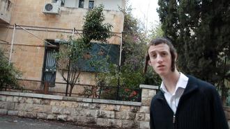 In einem jerusalemer Wohnviertel schaut ein junger Mann mit Schläfenlocken mit neugierig-überraschtem Blick in die Kamera.