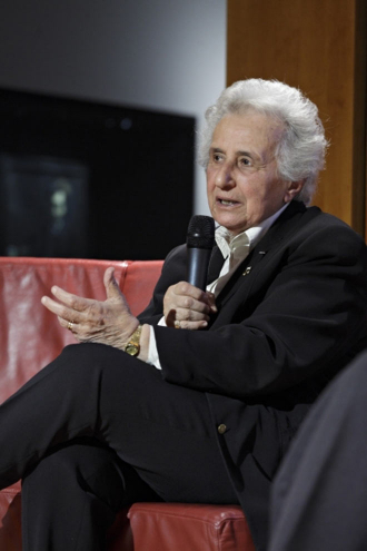 Ältere Damea mit Mikrofon im Sessel, sprechend