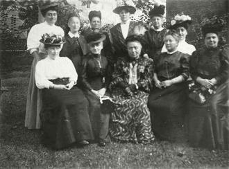 Gruppenbild von elf Frauen mit ausgefallenen Hüten in einem Garten