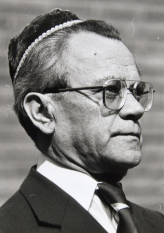 Black-and-white portrait of a man in semi-profile waring a kippah, glasses, a suit, and a tie