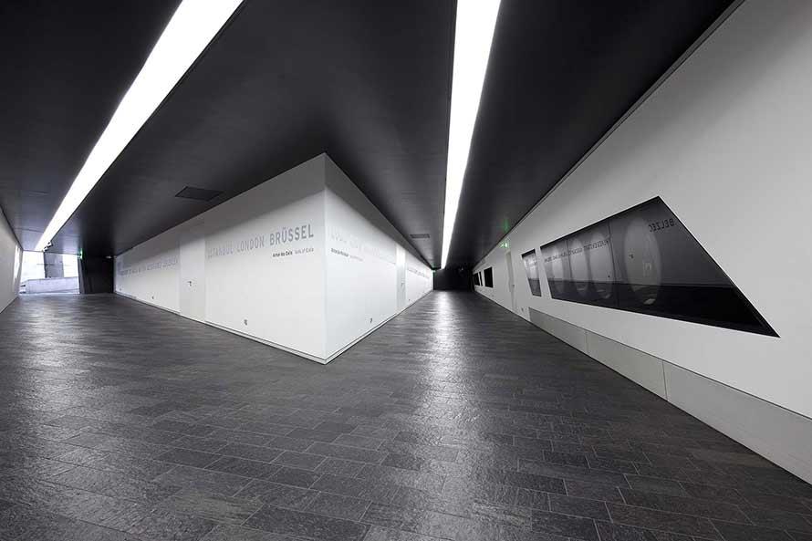 Zwei Gänge mit dunklen Schieferböden und weißen Wänden, in die Vitrinen eingelassen sind.