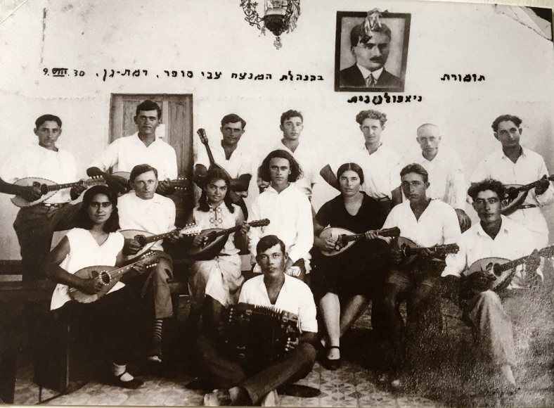 Group photo of 15 musicians with white shirts and mandolins